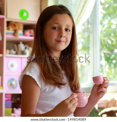 Sweet young girl in his room playing with toys and posing for the camera on the background of children's toys - stock photo