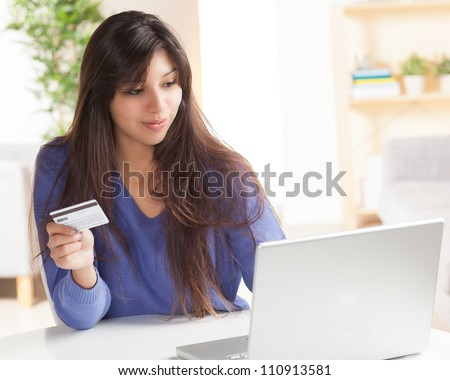 Sweet young Hispanic female using computer for online shopping holding credit card.