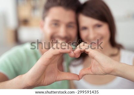Sweet Young Lovers Making Heart Shape using Bare Hands in Close up at Home. - stock photo