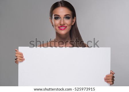 Sweet young woman with an awesome smile is full of positive feelings. Lady looks right in the camera and holds big paper tablet. Place for a funny text or for an image.