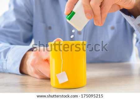 Sweetener tablets and hand with box whit cup of tea - stock photo