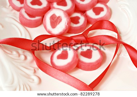 Sweetheart candy with matching satin ribbon tied in heart shape on elegant candy dish.  Macro with shallow dof. - stock photo