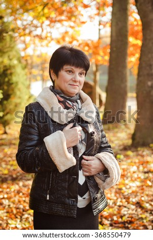 Sweetheart Mature brunette goes for a walk, resting in the autumn Park. Portrait of adult female in autumn. - stock photo