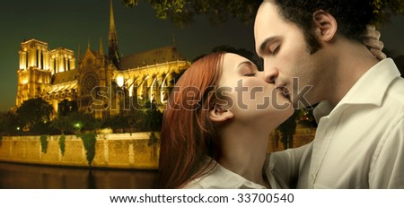 sweethearts kissing with notre dame de paris on the background - stock photo