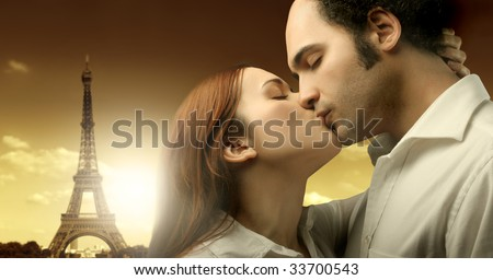 sweethearts kissing with tour eiffel on the background - stock photo