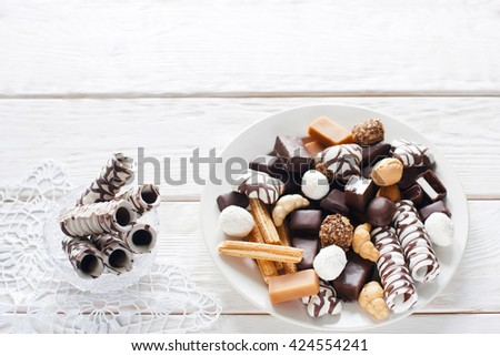 Sweets, chocolate candies, cookies on plate and chocolate sticks in vase on white wooden table top view. Vase on white lace napkin flat lay with copyspace. Chocolate candies set - stock photo