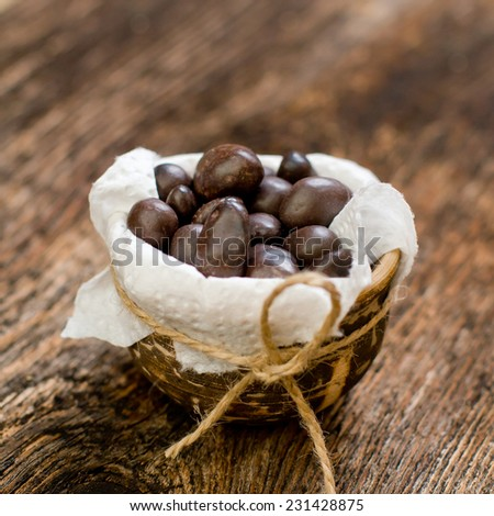 Sweets of chocolate in the pot on the backing of old wood  - stock photo