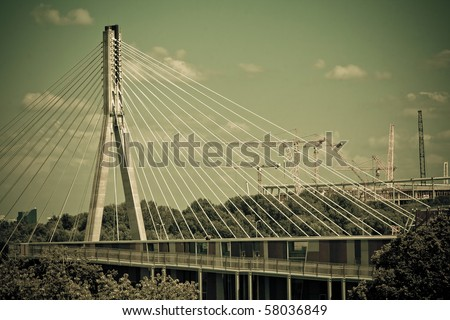 Swietokrzyski bridge on Vistula river in Warsaw. With cranes on construction site of National Stadium in background. Retro style. - stock photo