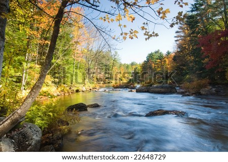 Swift river running across a colorful fall forest - stock photo