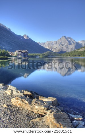 Swiftcurrent Lake, Many Glacier Hotel, and reflection in Glacier National Park - stock photo