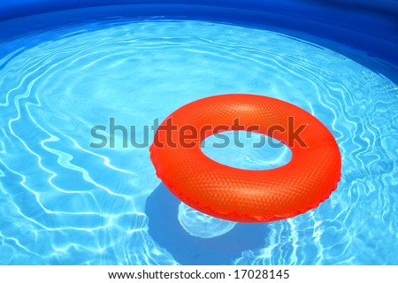 Swim ring inflatable floating on a sparkling blue swimming pool - stock photo