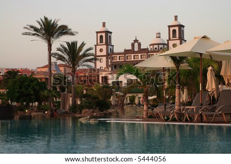 swiming pool at luxury hotel in spain with green palm and umbrellas