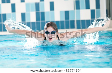 Swimmer breathing performing the butterfly stroke - stock photo