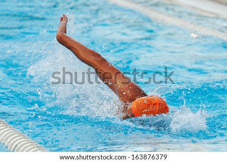 Swimmer in a pool with a orange cap - stock photo