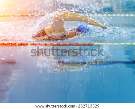 Swimmer in a race with water reflection - stock photo