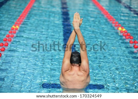 swimmer in cap raising hands, preparing to swim in sunny blue water swimming pool - back view  - stock photo