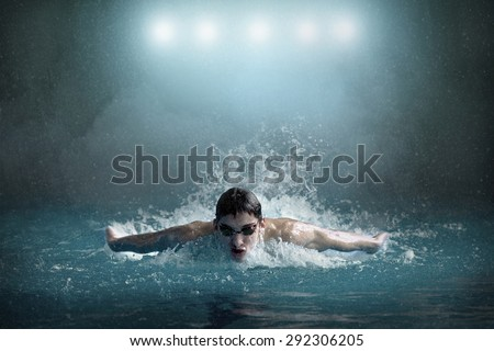 Swimmer in waterpool. Butterfly style. - stock photo