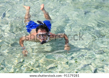 Swimmer snorkeling into a turquoise lagoon, surrounded by tropical multicolored fish