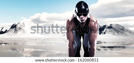 Swimmer triathlon muscled man with cap and glasses outdoor at a frozen lake with snow mountains and blue cloudy sky. Extreme fitness sport.