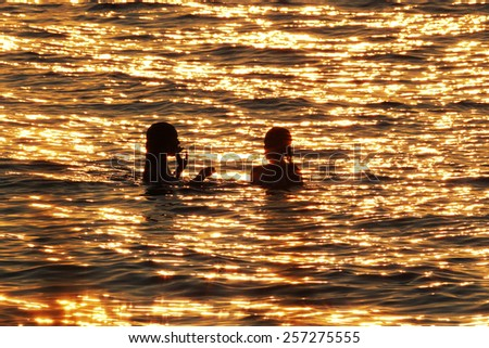 Swimmers in Lake Huron at Sunset - stock photo
