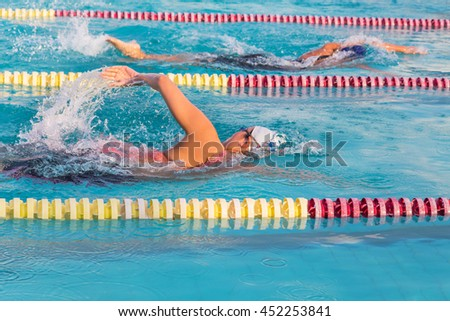 swimmers swimming front crawl in the pool - stock photo