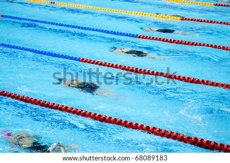 swimmers swimming in a pool - stock photo