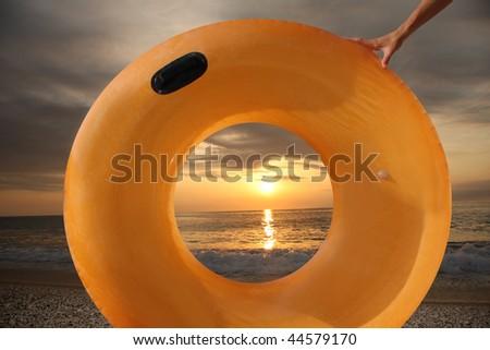 swimming belt against sunset on the beach - stock photo