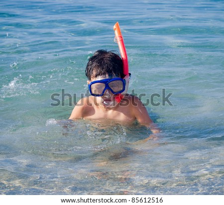 Swimming boy with snorkel mask in the sea - stock photo