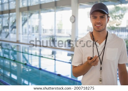 Swimming coach standing by the pool smiling at camera at the leisure center - stock photo