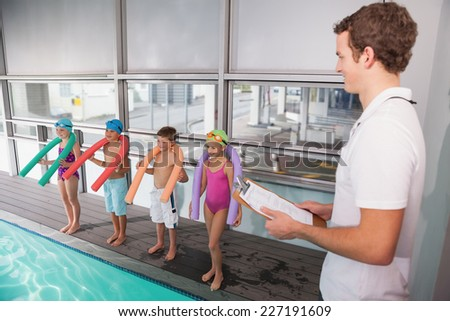 Swimming coach with his students poolside at the leisure center - stock photo