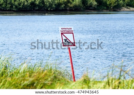 swimming forbidden - no swimming sign on Russian language on the shore sign against blue river