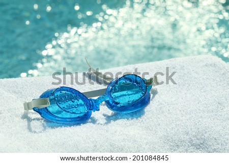 Swimming goggles on towel at  poolside  - stock photo