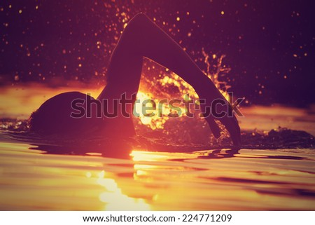 Swimming in sunset/sunrise. - stock photo
