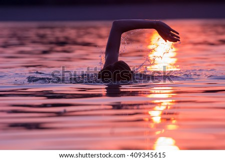 Swimming in sunset/sunrise with tropical colors. - stock photo