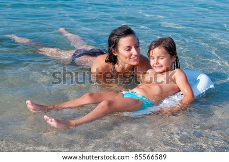 Swimming lesson. Little girl and her mother swimming in the sea. - stock photo