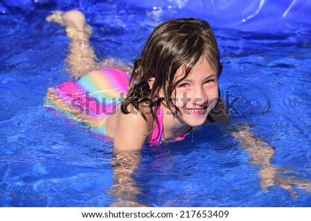 Swimming lessons: Child is learning how to swim in the pool