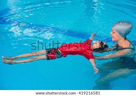 Swimming lessons for children - Swimming instructor helping little boy to relax in water - stock photo