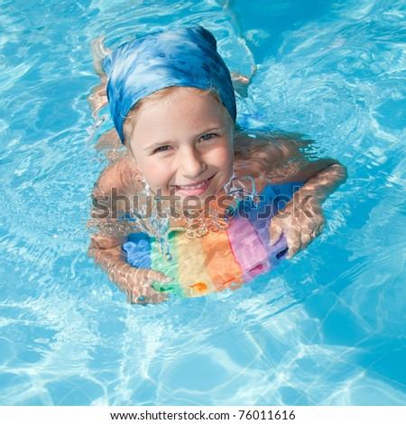 Swimming - little girl playing in blue water - stock photo
