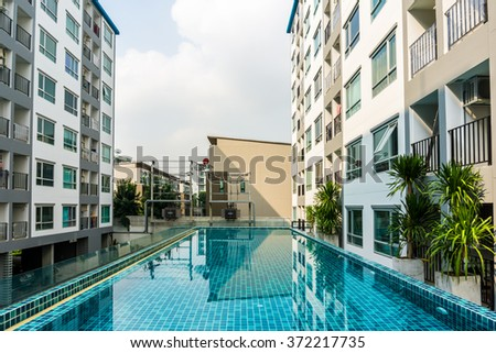 Swimming pool among high rise condo buildings, condominium with pool - stock photo