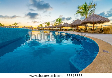 Swimming pool and a grass beach umbrellas with lounges at night, dawn, evening time at the luxury Caribbean, tropical resort. - stock photo