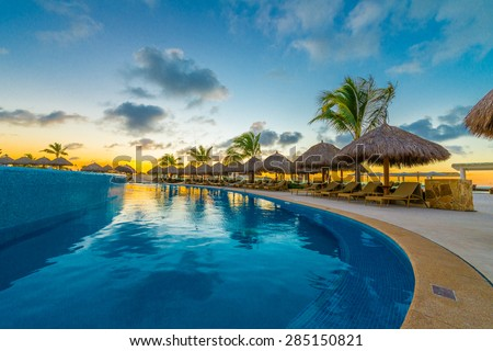 Swimming pool and a grass beach umbrellas with lounges at night, dawn, evening time. Mexico. - stock photo