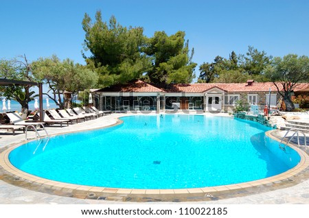 Swimming pool and bar  by a beach at the luxury hotel, Halkidiki, Greece - stock photo