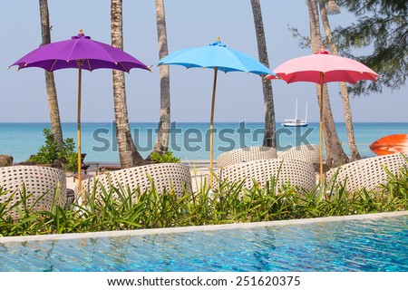 Swimming pool and beach chairs near the sea, Thailand - stock photo