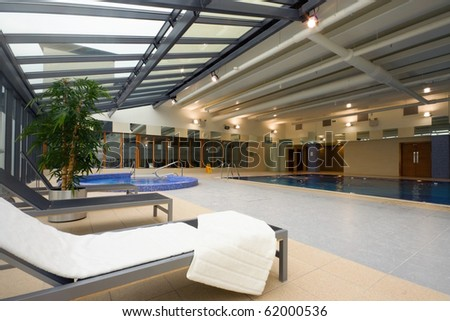 swimming pool and chaise-longue with towel in Hotel Leisure Center Interior - stock photo