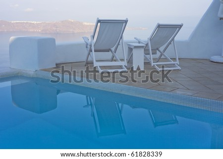 Swimming pool and deck chairs with sea view - stock photo