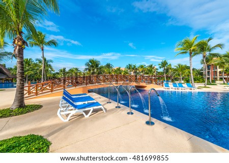 Swimming pool and decorative bridge and some lounges at the tropical, caribbean resort.