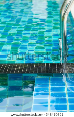 Swimming pool and entrance ladder to azure water