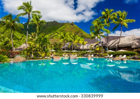Swimming pool and houses of tropical resort on Moorea, Tahiti - stock photo