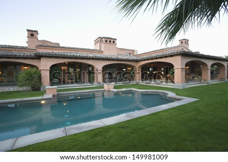 Swimming pool and lawn in front of spacious house against clear sky - stock photo