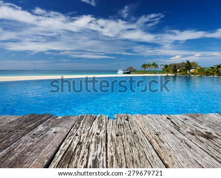 Swimming pool and old wooden pier in the tropical hotel  - stock photo